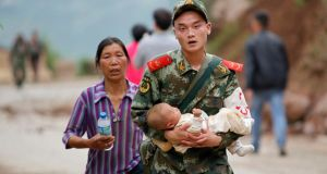 A paramilitary policeman carries a baby in his arms after an earthquake hit Ludian county of Zhaotong, Yunnan province today. Photograph: China Daily/Reuters