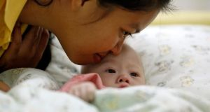 Gammy, a baby born with Down syndrome, is kissed by his surrogate mother Pattaramon Janbua at a hospital in Chonburi province. Photograph: Damir Sagolj /Reuters