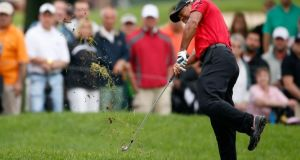 Tiger Woods grimaces as he hits his second shot   out of the rough beside a bunker on the second hole during the final round of the WGC-Bridgestone Invitational at Firestone Country Club in Akron, Ohio. The former world No 1 admitted after withdrawing from the tournament that he jarred his back on the shot. Photograph: Gregory Shamus/Getty Images