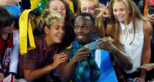 Jamaica's Usain Bolt poses for photographs with fans after Jamaica won the relay final at the 2014 Commonwealth Games in Glasgow. Photograph: Reuters