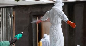 A Liberian nurse in protective clothing being sprayed with disinfectant after preparing several bodies of victims of Ebola for burial in the isolation unit of the ELWA Hospital in Monrovia, Liberia. Photograph: Ahmed Jallanzo/EPA/