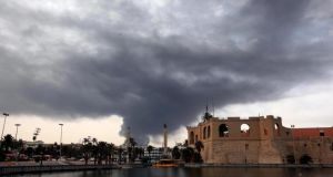 Smoke darkening the sky over Tripoli's Assaraya Alhamra Museum after rockets fired by one of Libya's militias struck and ignited a tank in the capital's main fuel depot, Tripoli, Libya yesterday.  Photograph: EPA/Sabri Elmhedwi