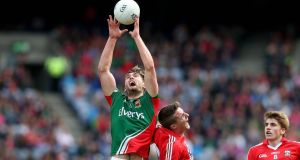 Mayo's Aidan O'Shea wins this aerial duel with Cork's Aidan Walh in yesterday's GAA Football All Ireland football quarter-final at Croke Park. Mayo will now face Kerry, who beat Galway in yesterday's other quarter-final, in three weeks time. Photograph: Donall Farmer/Inpho