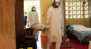 In this handout provided by Samaritan's Purse, two people in protective clothing carry a body at an Ebola isolation ward at a mission hospital outside of Monrovia, Liberia. Photograph:  Samaritans Purse via Getty Images