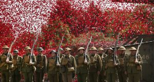 Members of the Great War Society living history group dressed as members of the 4th Battalion, the Middlesex Regiment, stand under a shower of poppy flowers at the Tank Museum, Bovington, England. Photograph: Peter Macdiarmid/Getty Images