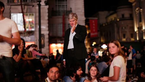 A man lost in thought amid crowds at Piccadilly Circus as memorial images of the war are shown.  Photograph: Matthew Lloyd/Getty Images