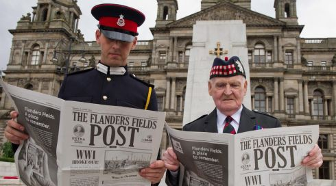 Officer Cadet Christopher Miller (left) and retired Sgt Ken Long (83), reading a reproduction of a first World War era newspaper at the Cenotaph in Glasgow, Scotland. Photograph: Bombardier Murray Kerr/EPA