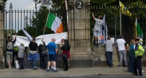 Protesters climbed up on railings to heckle outside Glasnevin Cemetary during a ceremony attended by President Michael D Higgins and the Duke of Kent earlier this week. Photograph: Brenda Fitzsimons / The Irish Times