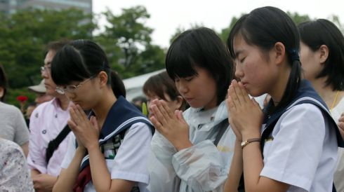 Students offer prayers for victims killed by what was the world's first atomic bombing as a weapon of war. Photograph: Kimimasa Mayama/EPA