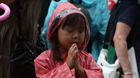 A child prays at Hiroshima Peace Memorial Park.  Photograph: Buddhika Weerasinghe/Getty Images