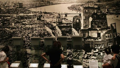 Visitors look at a post-bombing picture of the convention centre that is now the Atomic Bomb Dome in Hiroshima. Photograph: Junko Kimura/Getty Images