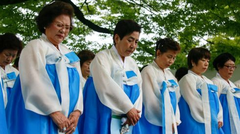 South Korean residents of Japan offer a silent prayer for Korean victims. Photograph: Kimimasa Mayama/EPA