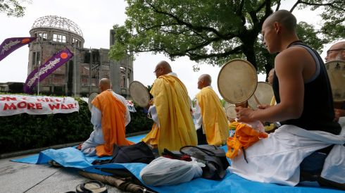 Buddhist monks offer prayers. Photograph: Kimimasa Mayama/EPA