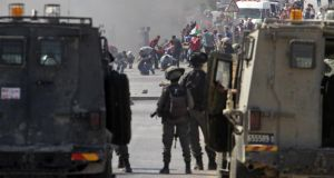 Palestinian protesters hurl stones at Israeli soldiers during clashes at Bet Forik checkpoint near the West Bank city of Nablus, yesterday, during a protest against Israel attacks on the Gaza Strip. Photograph:  EPA
