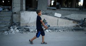 A Palestinian boy carries copies of the Koran from a badly damaged mosque, which witnesses said was hit in an Israeli air strike, in Gaza City today. Photograph: Reuters
