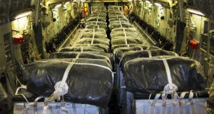 A handout picture made available by the US department of defense today  shows pallets of bottled water being loaded aboard a US Air Force C-17 Globemaster III aircraft in preparation for a humanitarian airdrop over Iraq.