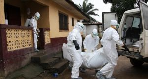 Liberian nurses take the body of an Ebola victim  from a home in St. Paul Bridge Community on the outskirts of Monrovia, Liberia yesterday. Photograph: EPA