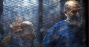 Muslim Brotherhood senior member Mohamed El-Beltagy (L) gestures the group's four-fingered Rabaa hand symbol next to Islamist cleric Safwat Hegazis as they are held in  the defendant's cage, at a courtroom in Cairo. An Egyptian court has today moved to dissolve the political wing of the Muslim Brotherhood. Photograph: Amr Abdallah Dalsh/Reuters.