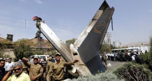 Iranian soldiers  stand near the tail of a crashed airplane in Tehran today. Photograph: EPA