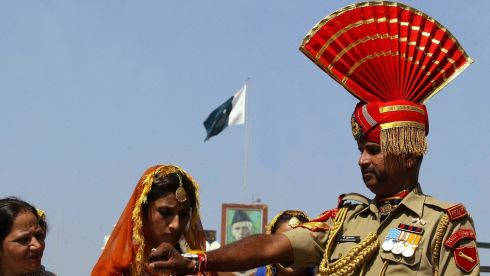 "An Indian woman ties a ""Rakhi"" or traditional Indian sacred thread onto the wrist of an Indian Border Security Force soldier during the Raksha Bandhan celebrations at the India-Pakistan joint check post at the Wagah border on the outskirts of the northern Indian city of Amritsar. Photograph: Munish Sharma/Reuters"