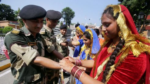 Indian girls in traditional attire tie Rakhi on the wrists of Indian Border Security Force soldiers on the occasion of Raksha Bandhan festival, at the Indian-Pakistani joint check post at Attari. Photograph: Raminder Pal Singh