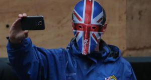 A loyalist protester takes photographs at the march in Belfast today.  Photograph: Niall Carson/PA Wire