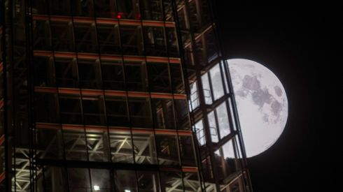 A view of the 'supermoon' rising behind The Shard building in  London. The phenomenon, known as a perigee full moon, causes higher tides as it reaches its closest point to Earth. Photograph Yui Mok/PA Wire