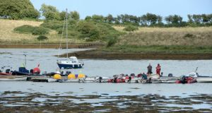 Some of the rescued dinghies at the East Down Yacht Club are attended to by rescue workers  in Strangford. Photograph: Getty
