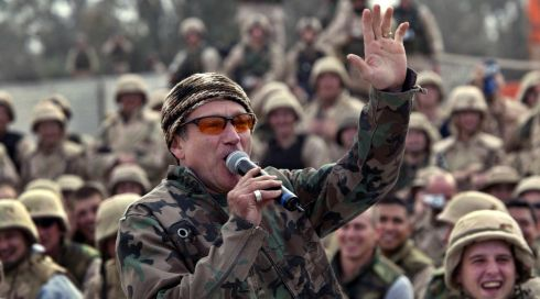 The comedian, wearing a camouflage jacket, entertains a cheering crowd of US troops at Baghdad airport in December, 2003. Photograph: REUTERS/Petar Kujundzic