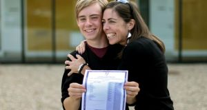 Mark Berney at Gorey Community College, Co Wexford, with his mother Nicky Deacon, holding a copy of his Leaving Cert results with 9 A1s last year. Photograph: Julien Behal