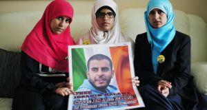 Omaima, Fatima and Somaia Halawa, holding a photo of their brother Ibrahim, who is still in prison in Egypt.  Photograph: Aidan Crawley/The Irish Times