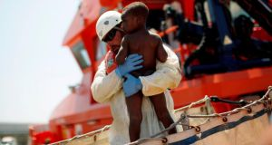A worker carries an African child immigrant who arrived on a rescue ship at the southern Spanish port of Tarifa, near Cadiz in southern Spain yesterday.  Photograph: Reuters/Jon Nazca