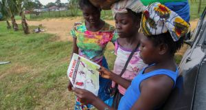 Liberian girls read an Ebola sensitisation pamphlet in Monrovia, Liberia. Photograph: Ahmed Jallanzo/EPA