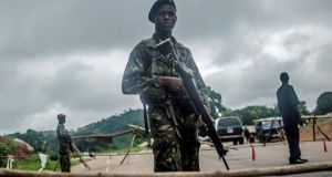 "Soldiers stand guard at a roadblock outside Kenema, Sierra Leone. Governments in the region have revived the ""cordon sanitaire,"" in which a line is drawn around the infected area and no one is allowed out. Photograph: Tommy Trenchard/the New York Times"
