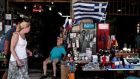 Tourists walk past a shop in Athens yesterday.  Greece's economy shrank in the second quarter at its slowest annual pace since late 2008 when its protracted recession began. Photograph: Alkis Konstantinidis/Reuters