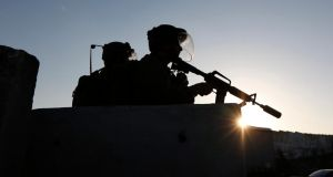Israeli soldiers during a protest by Palestinians against the Israeli offensive in Gaza at a checkpoint near Ramallah yesterday. Photograph: Mohamad Torokman/Reuters
