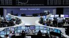 Traders working at their desks in front of the DAX board at the Frankfurt stock exchange yesterday. Photograph: Reuters