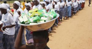 A girl sells soap as women pray for an end of the Ebola epidemic in Monrovia, Liberia. Photograph: John Moore/Getty Images