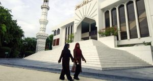 Maldivian women walk past the Grand Friday Mosque in the island capital of Malé. Few visitors get to see the reality of life for locals in the Indian Ocean archipelago who live in an increasingly harsh regime under President Abdulla Yameen Abdul Gayoom. Photograph: AFP  Lakruwan Wanniarachchi/AFP/Getty Images
