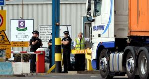 A group of Police Officers stand by the main entrance to Tilbury Docks in Essex, where a shipping container was found with 31 illegal immigrants were found inside with one dead and the rest ill and taken to hospital. Photograph: PA