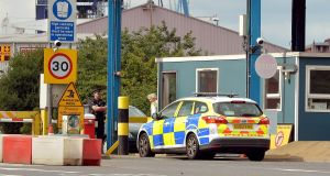 A police car arrives at the main entrance to Tilbury Docks in Essex, where a shipping container was found with illegal immigrants inside with one dead and the rest ill and taken to hospital. Photograph: John Stillwell/PA Wire