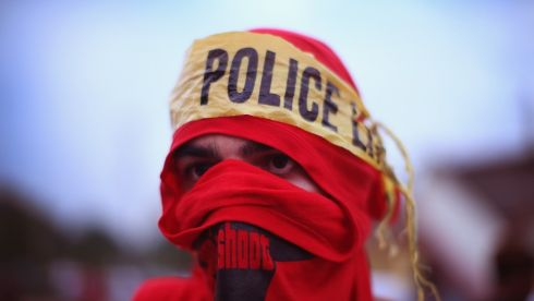 A demonstrator wears a makeshift headscarf with police tape around it as he takes part in a protest. Photograph: Scott Olson/Getty Images