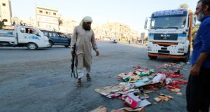 An Islamic State fighter keeps guard as  employees of the group, hired to monitor and check the quality of goods in markets, throw away confiscated products in central Raqqa. Photograph: Reuters