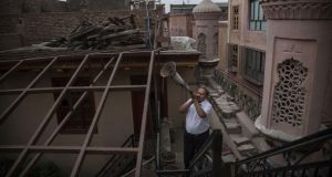 A Uyghur Muslim muezzin uses a bullhorn to call the evening prayers in Kashgar. Photograph: Kevin Frayer/Getty Images