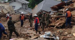 Japan self-defence force soldiers and rescue workers search for survivors as a site where a landslide swept through a residential area at Asaminami ward in Hiroshima, western Japan. Photograph: Joint Staff of the Defence Ministry of Japan/Handout via Reuters.