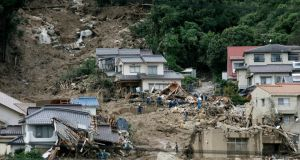 Rescue workers search for missing people at a landslide site in Hiroshima,  Japan today. At least 27 people are dead and 10 unaccounted for in landslides triggered by torrential rain in the western Japanese city. Photograph: Kimimasa Mayama/EPA.