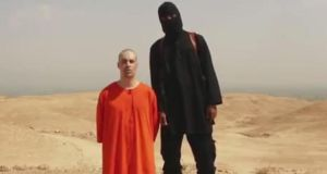 The Islamic State video showing Jame's Foley's murder is titled 'A Message to America' and shows the journalist on his knees, head shaven and hands tied behind his back, in an orange jumpsuit like those worn by the Muslim prisoners of Guantánamo. A hooded Islamic State militant, dressed in black, stands beside him in the desert, wielding a knife. Photograph: AP Photo