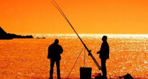 David Sleator's work: early-morning fishermen enjoy the sunshine at Dalkey harbour in 2003.