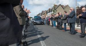 A guard of honour of fellow photographers applauds as the hearse carrying the coffin of David Sleator leaves Rialto in Dublin for the burial in Deansgrange cemetery yesterday. Photograph: Provision