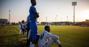 Older African members of the Aspire Football Dreams program watch as younger players played the visiting FC Barcelona youth team, in Doha, Qatar, on January 27th, 2014. Photograph: Bryan Denton/The New York Times